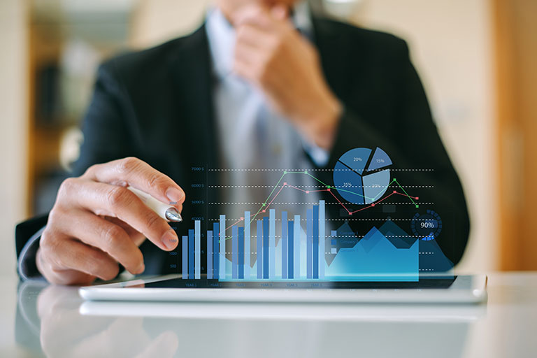Businessman looking at 3D bar graph and pie chart depicted over tablet