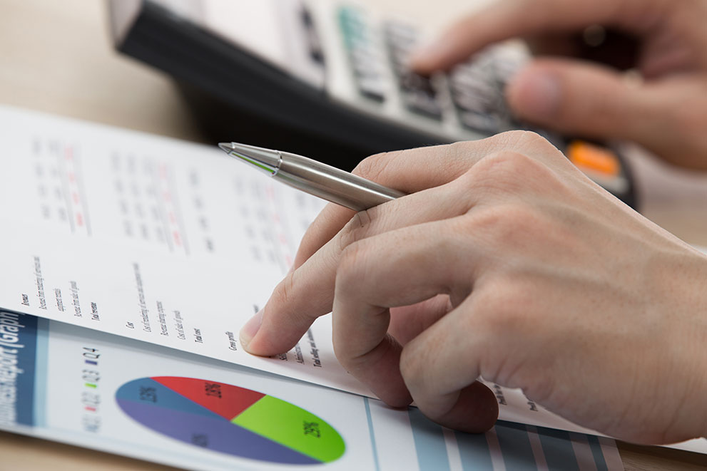 close up of hand pointing to data with a pie chart and calculator