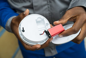 Man showing holding 9V battery and smoke detector